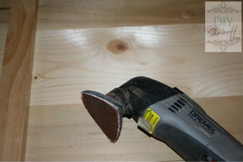 sanding edges of wood plank sign