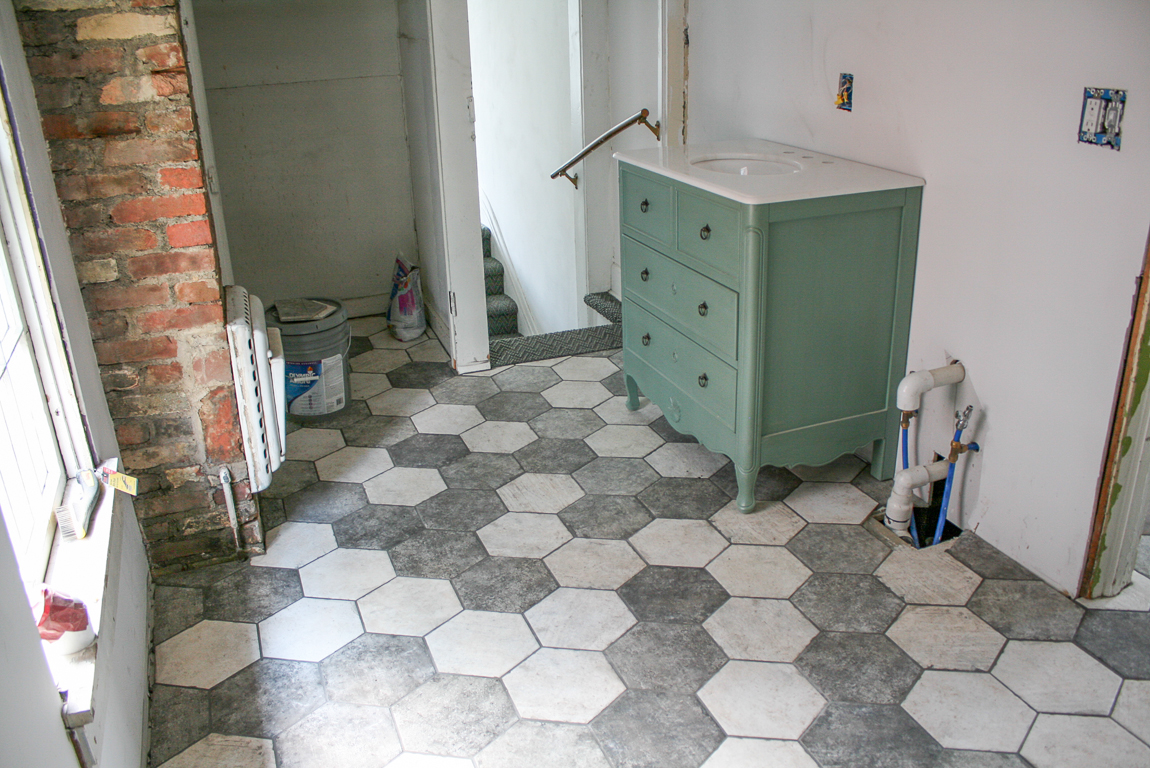 bathroom makeover with hexagon tile floor and blue vanity